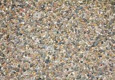 Färgrik abstrakt bakgrund av små kiselstenar och stenen inbäddade i cement royaltyfria bilder