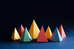 Färgrik abstrakt geometrisk form figurerar stilleben Rektangulär kub för tredimensionell pyramidprisma på svartblått Arkivfoto