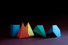 Färgrik abstrakt geometrisk form figurerar stilleben Rektangulär kub för tredimensionell pyramidprisma på svartblått Royaltyfri Fotografi