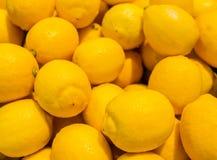 Färgrik bakgrund av citroner i marknad Arkivfoto