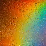 Färgrik bakgrund med droppar av vatten arkivbild