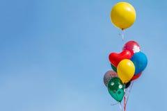 Färgrik ballong som svävar i mitt- luft mot en ljus blå himmel Arkivfoto