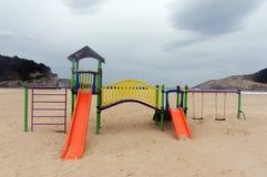 Färgrik barnlekplats på stranden Arkivfoton