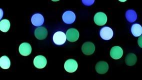 Färgrik blinkajulbokeh tänder på kretsad svart bakgrund stock video