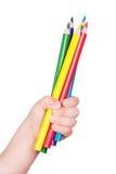 Färgrik blyertspenna i den isolerade barnhanden Royaltyfria Foton