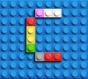 Färgrik bokstav C från byggnadslegotegelstenar på blå legobakgrund Lego bokstav M Fotografering för Bildbyråer
