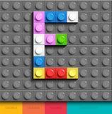 Färgrik bokstav E från byggnadslegotegelstenar på grå legobakgrund Lego bokstav M Royaltyfria Bilder
