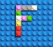 Färgrik bokstav F från byggnadslegotegelstenar på blå legobakgrund Lego bokstav M Royaltyfria Foton