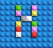 Färgrik bokstav X från byggnadslegotegelstenar på blå legobakgrund Lego bokstav M Arkivfoto