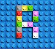 Färgrik bokstav R från byggnadslegotegelstenar på blå legobakgrund Lego bokstav M Arkivbilder