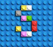 Färgrik bokstav S från byggnadslegotegelstenar på blå legobakgrund Lego bokstav M Arkivbild