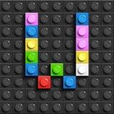 Färgrik bokstav W från byggnadslegotegelstenar på svart legobakgrund Lego bokstav M Royaltyfri Fotografi