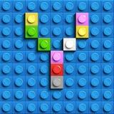 Färgrik bokstav Y från byggnadslegotegelstenar på blå legobakgrund Lego bokstav M Fotografering för Bildbyråer