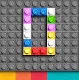 Färgrik bokstavsnolla från byggnadslegotegelstenar på grå legobakgrund Lego bokstav M Arkivfoto
