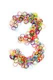 Färgrik elastisk gummibandform nummer tre fotografering för bildbyråer