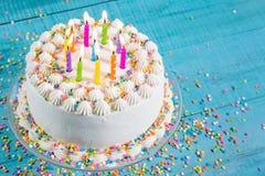 Färgrik födelsedagkaka med stearinljus Arkivfoto
