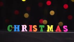 Färgrik ` för ord`-jul från mång--färgade träbokstäver framme av abstrakt suddig ljusbokehbakgrund stock video