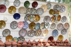 Färgrik fajanskrukmakeridisk och tajines på skärm i Morocc Arkivbilder