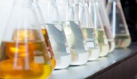 Färgrik flytande i flaskor som lägger på hylla Arkivbilder