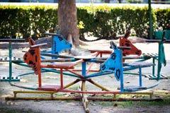 Färgrik gammal och rostig järnkarusell på lekplats Arkivbilder