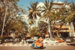 Färgrik gata med palmträd och rusamopeden på den upptagna vägen Royaltyfria Bilder
