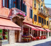 Färgrik gata med tabeller av kafét på en solig morgon, Venedig, Italien royaltyfria bilder