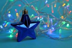 färgrik girland på en blå bakgrund med en leksak i form av en stjärna arkivfoton