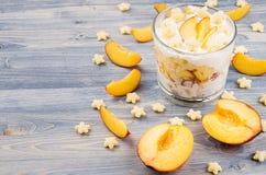 Färgrik gladlynt frukost med yoghurten, persika för skiva för stjärnacornflakes mogen på blått wood bräde Dekorativ gräns med kop Arkivbild