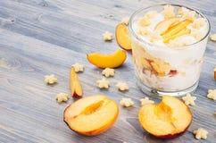 Färgrik gladlynt frukost med yoghurten, persika för skiva för stjärnacornflakes mogen på blått wood bräde Dekorativ gräns med kop Royaltyfri Foto