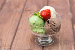Färgrik glass med jordgubbar på en träbakgrund Arkivbild