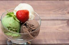 Färgrik glass med jordgubbar på en träbakgrund Arkivfoton