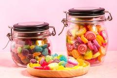 Färgrik godis i flaska på rosa bakgrund Arkivfoton