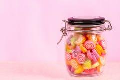 Färgrik godis i flaska på rosa bakgrund Arkivfoto