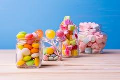 Färgrik godis i krus på selektiv fokus för trätabell Royaltyfri Foto