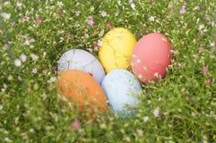 Färgrik gräns för påskägg vid gruppen av blommabakgrund Arkivfoton