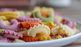 Färgrik gräsplan, guling, vit, apelsin och italiensk kronapasta för rosa färger på den vita plattan som blir på trätabellen, närb Royaltyfri Foto