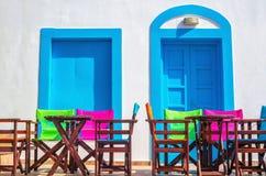 Färgrik grekisk restaurangtabell och stolar framme av iconic bl Royaltyfri Fotografi