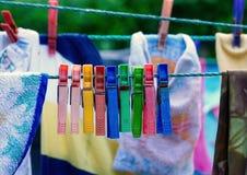 Färgrik grupp av mycket gamla och använda klädnypor på ett rep Arkivfoto