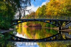 Färgrik höst i parkera, den gamla bron och de härliga vattenreflexionerna Arkivbilder