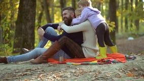 Färgrik höstfamiljstående Lyckliga le unga föräldrar med den lilla sonen som lägger i höstsidor Unga föräldrar och stock video