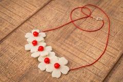 Färgrik halsband för pärlor för filt för för blommaformträ som och ull är handgjord med färgpärlor på en wood tabell arkivbilder