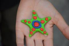 Färgrik handgjord stjärna i childrenÂs hand royaltyfri fotografi