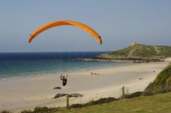 Färgrik Hang Glider Flying Over Porthmeor strand, St Ives, Cornwall. Arkivbilder