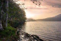 Färgrik himmel- och solljusström över bergsjön i sommarse royaltyfri foto