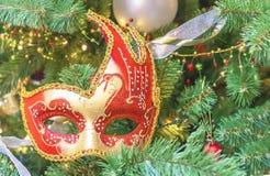 Färgrik karnevalmaskering på bakgrunden av julgranen arkivbilder