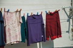 Färgrik kläder hängde för att torka framme av byggnad royaltyfri bild