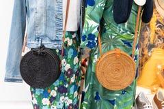 Färgrik kläder och påsar på kuggar i en modeboutique arkivfoton
