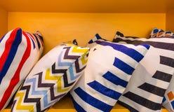 Färgrik kudde- och designmodell på gul hylla Moderna kuddar och inre möblemang royaltyfria foton
