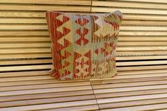 Färgrik kudde på en träbänk Royaltyfri Bild