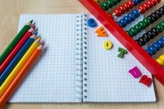 Färgrik kulram, blyertspennor, klocka, svart tavla på träbakgrunden Utbildning tillbaka till skolan royaltyfri bild
